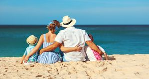 Happy family father, mother and children backs on beach at sea stock photos
