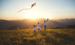 Happy family father,  mother and children launch  kite on nature Stock Photography