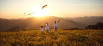 Happy family father, mother and children launch kite on nature. Happy family father, mother and children launch a kite on nature at sunset royalty free stock photo