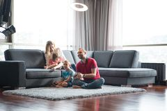 Happy family playing a video game. Happy family. Father, mother and children playing a video game Father and son playing video games together on the floor Stock Photo