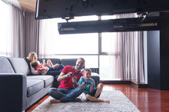 Happy family playing a video game. Happy family. Father, mother and children playing a video game Father and son playing video games together on the floor Royalty Free Stock Image