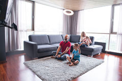 Happy family playing a video game. Happy family. Father, mother and children playing a video game Father and son playing video games together on the floor Stock Image
