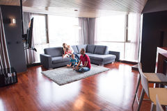 Happy family playing a video game. Happy family. Father, mother and children playing a video game Father and son playing video games together on the floor Royalty Free Stock Images