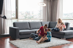Happy family playing a video game. Happy family. Father, mother and children playing a video game Father and son playing video games together on the floor Stock Photography