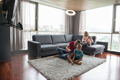 Happy family playing a video game. Happy family. Father, mother and children playing a video game Father and son playing video games together on the floor Royalty Free Stock Photography
