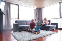 Happy family playing a video game. Happy family. Father, mother and children playing a video game Father and son playing video games together on the floor Stock Images