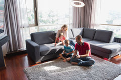 Happy family playing a video game. Happy family. Father, mother and children playing a video game Father and son playing video games together on the floor Stock Photos