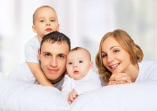 Happy family of father, mother and children in white bed Royalty Free Stock Photo