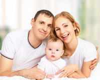 Happy family of father, mother and small baby girl daughter in stock image