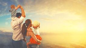 Happy family of father, mother and two children, baby son and da. Ughter on the beach at sunset royalty free stock images