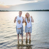 Happy family - father, mother, two sons on the beach with their feet in the water at sunset. They are all smiling, looking at the camera. Outdoor portrait Royalty Free Stock Photos