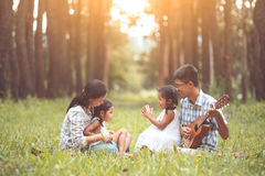 Happy family father playing guitar with mother and child. Happy family father playing guitar, mother and two little child girls sing a song, family having fun royalty free stock photo