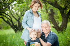 Happy family. Father and son listening pregnant mother's belly. royalty free stock image