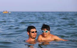 Happy family with father and son playing in the sea Stock Images