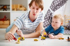 Happy family father and son playing in toy car in playroom. At home Royalty Free Stock Image
