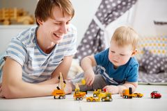 Happy family father and son playing in toy car in playroom. At home Stock Photos