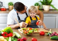 Happy family father with son preparing vegetable salad Royalty Free Stock Photography