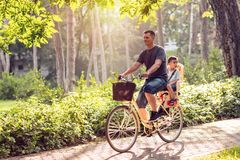 Happy family. Father and son riding bike in the park Stock Photos