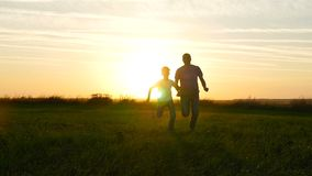Happy family father and son running across the green field against the sunset background