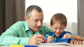 Happy family: father and son spend time painting with colored markers.