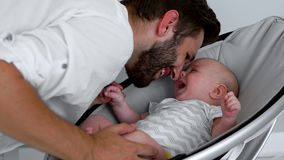 Happy family father and son spend time together and smile at each other. Modern interior of a light Studio. Proud father holding his newborn baby daughter in stock video