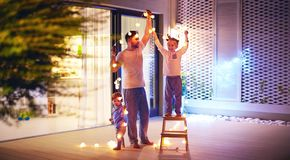 Happy family, father with sons decorate open space patio area wi. Happy family, father with two sons decorate open space patio area with christmas garlands royalty free stock photography