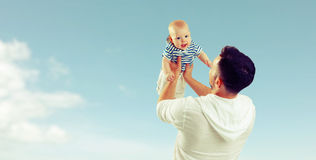 Happy family father throw up baby son on sky Stock Photos