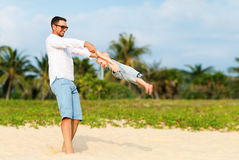 Happy family father turns baby son on beach Stock Photography