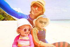 Happy family father and two kids at beach making Stock Photo