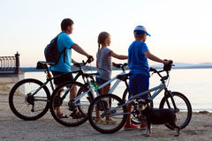 Happy family - father with two kids on bikes with dog Stock Photos