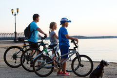 Happy family - father with two kids on bikes with dog Stock Photo