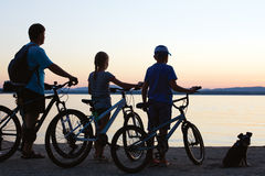 Happy family - father with two kids on bikes with dog Royalty Free Stock Image