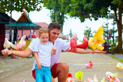 Happy family feeding colorful pigeons on animal farm Royalty Free Stock Photography