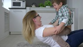 Happy family, female with child having fun lying on floor at home. Closeup stock video footage