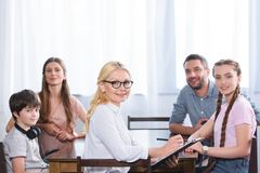 Happy family and female counselor with clipboard in hands on therapy session looking at camera. In office stock photos