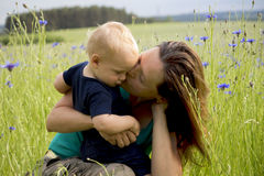 Happy family in the field of blew flowers. Beautiful young mother kisses her adorable baby boy. Concept of happiness Royalty Free Stock Photography