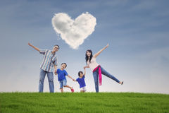 Happy family at field with heart symbol. Image of cheerful asian family holding hands on the meadow with cloud shaped heart symbol Royalty Free Stock Photography