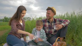 Happy family in field, smiling happy female pours milk into glass of kid boy and man while relaxing outdoors in green stock footage