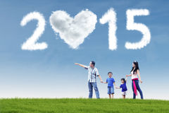 Happy family in field under cloud of 2015. Attractive young asian family walking in field and holding hands under cloud of 2015 Stock Photography