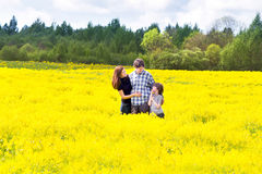 Happy family in a field of yellow flowers. Happy young family in a field of yellow flowers Stock Image
