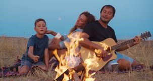 Happy family by fire during picnic on beach in the evening. Happy family by fire during picnic on beach in the evening stock footage