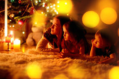 Happy family by a fireplace on Christmas Stock Images