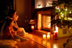 Happy family by a fireplace on Christmas. Young mother and her two little daughters sitting by a fireplace in a cozy dark living room on Christmas eve Royalty Free Stock Image
