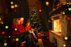 Happy family by a fireplace on Christmastime Stock Image