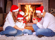 Happy family by fireplace Stock Photos