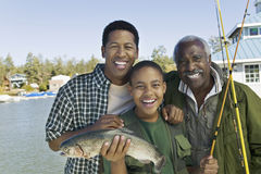 Happy Family With Fishing Rod And Fish. Portrait of happy three generation family with fishing rod and fish at lake stock photography