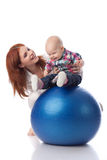 Happy family with  fitness ball. Mother and sweet small baby with fitness ball on a white background Stock Photography