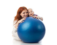 Happy family with  fitness ball. Mother and sweet small baby with fitness ball on a white background Royalty Free Stock Photography