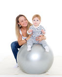 Happy family with fitness ball. Young mother and sweet small baby with fitness ball on a white background. Healthy family Royalty Free Stock Image