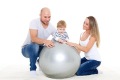 Happy family with fitness ball. Young parents and sweet small baby with fitness ball on a white background. Healthy family Stock Photo